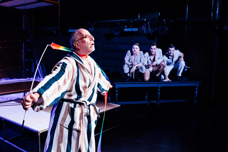 Scena ze spektaklu, aktor ubrany wszlafrok zaciska wstążkę do gimantyki na swojej szyi. Na drugim planie przyglądają sie mu trzej aktorzy ubrani wbeżowe komplety.