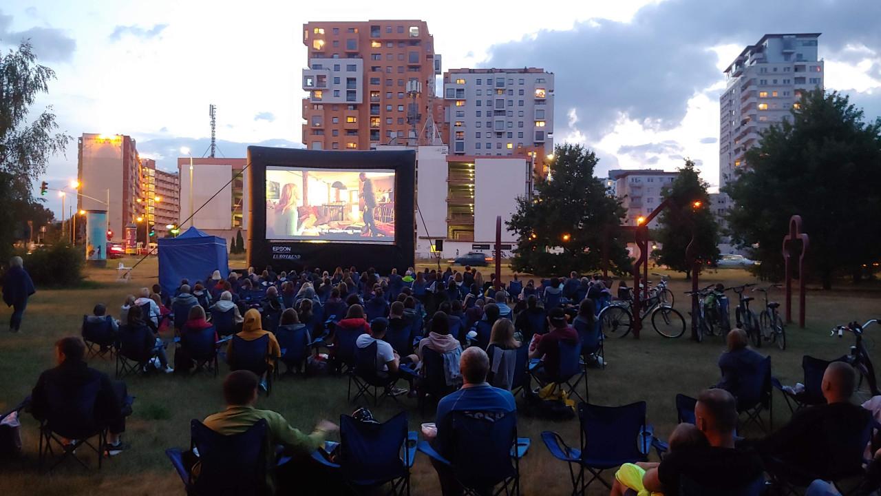 ludzie oglądający film na wielkim ukranie ustwionym wparku, wtle bloki mieszkalne