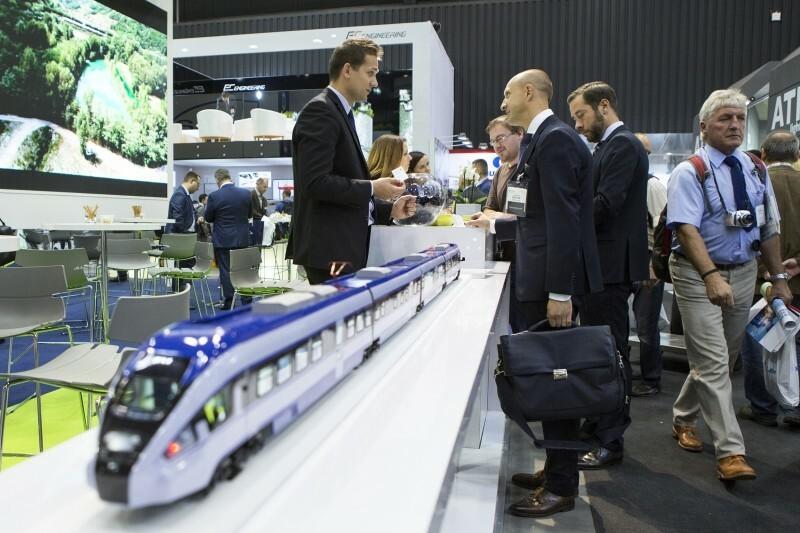 hala wystawowa, mężczyźni rozmawiający przy stoisku wystawienniczym, na ladzie położona jest replika niebieskiego tramwaju
