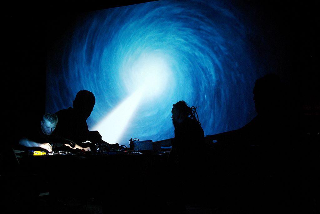 kontury dwóch mężczyzn grających za konsoletą, wtle ekran zwyświetlanym obrazem białej kuli światła